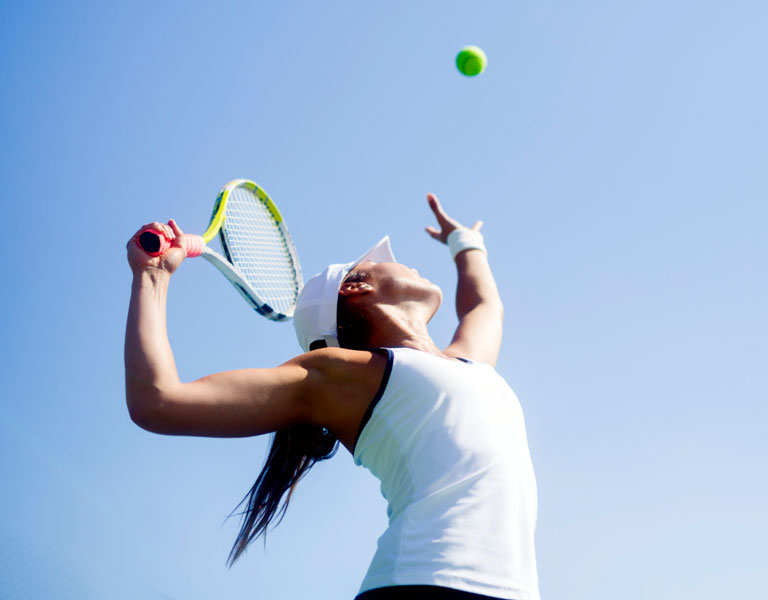 Photo of a female tennis player serving