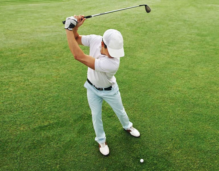 Photo of a male golfer taking a swing